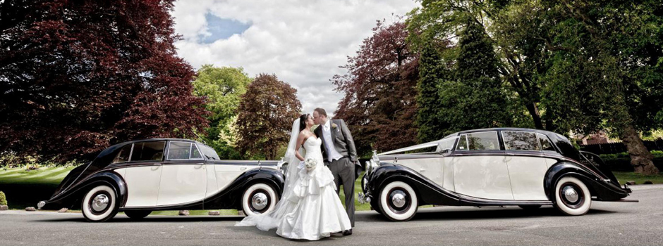 Harrogate Wedding Cars banner image - a couple photographed in front of two stylish wedding cars